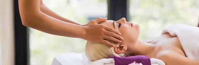 Massage Therapist giving a scalp massage.